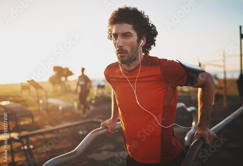 Obraz Portrait of an athletic young man listening to music on earphones doing exercise on parallel bars in the park - young man doing dips outdoors - fototapety do salonu