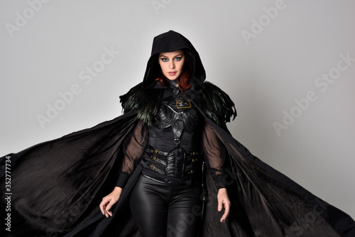 Stampa su Tela Close up fantasy portrait of a woman with red hair wearing dark leather assassin costume with long black cloak