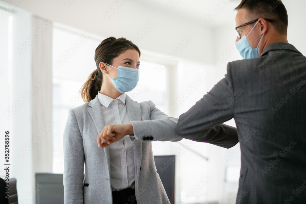Fototapeta Businessman and businesswoman with medical mask in office. Greetings in Covid-19 time.