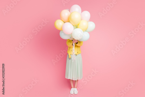 Photo Full length photo of funny playful lady hold hands many air balloons hiding faci