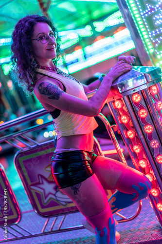 Fotografía a young woman in eighties clothes with curly hair posing in different attraction