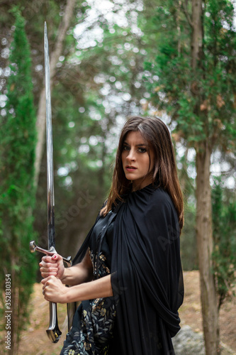 Photo young woman in the forest dressed in a tunic holding a large sword