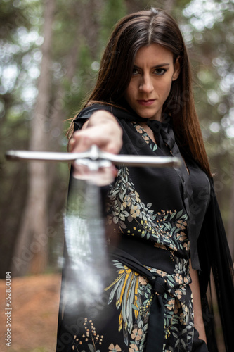 Photo Woman in the forest dressed in a tunic holding a large sword