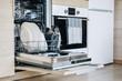 Leinwandbild Motiv Open dishwasher with white clean dishes after washing in modern scandinavian kitchen.