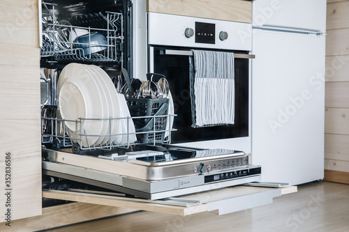 Photo Open dishwasher with white clean dishes after washing in modern scandinavian kitchen