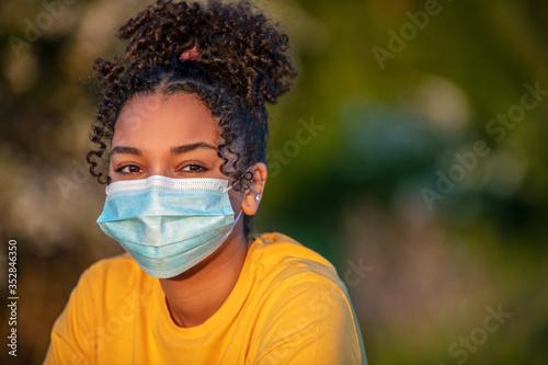 Fototapeta African American Teenager Girl Woman Wearing Coronavirus COVID-19 Face Mask in V