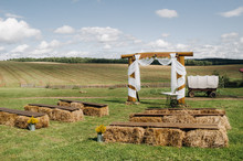 Wedding Ceremony On The Street In The Village Field.Decor With Haystacks And A Cart For A Wedding.Rustic Wedding Party.