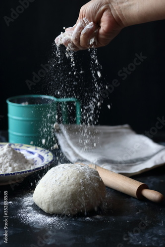 Dough ,making dough with flour on a black background, bread and pizza dough Fototapeta
