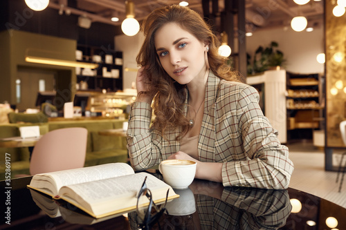 Fototapeta Young beautiful woman drinks coffee and reading book in cafe obraz