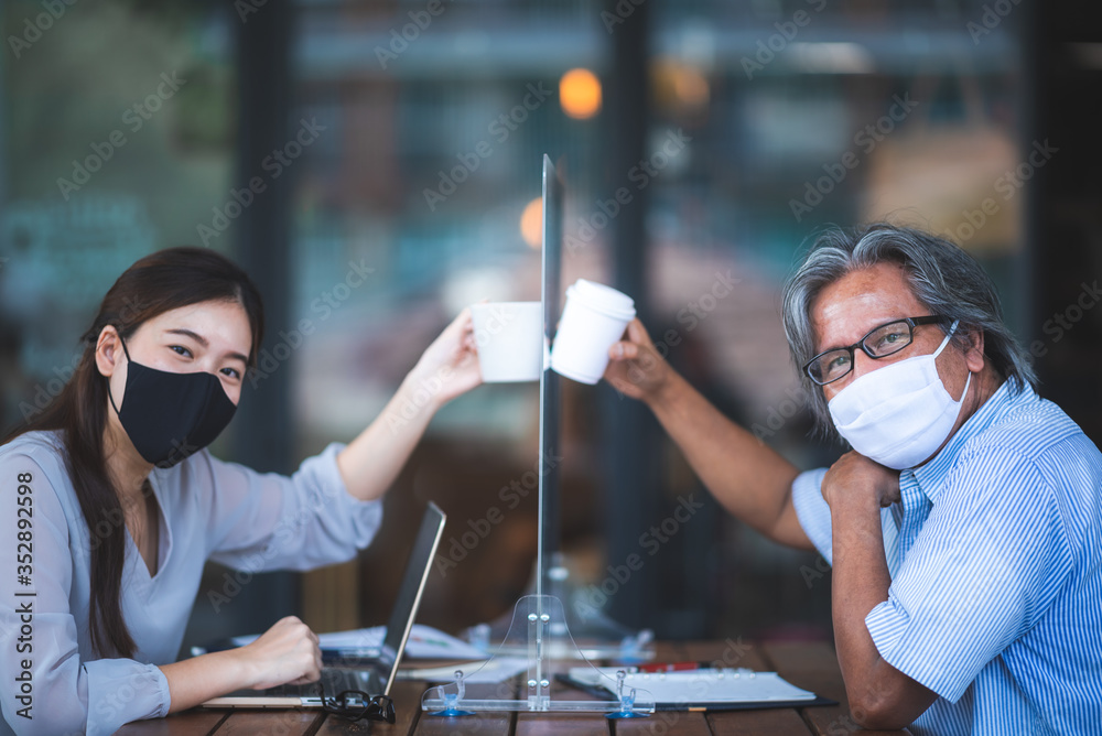 Fototapeta Asian business woman working in cafe with medical face mask and table shield, social distancing of the new normal lifestyle after epidemic of coronavirus COVID-19