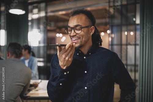 Foto Laughing young businessman talking on speakerphone at work