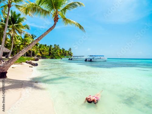 Fototapeta A young woman enjoying a sunny day at the beach in Saona Island in the Dominican Republic. obraz na płótnie