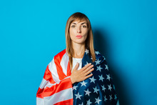 A Young Woman Wrapped In The USA Flag Makes A Hand Gesture On A Blue Background. USA Visa Concept, English Language, Gesture Is All Right, Thumbs Up, Like