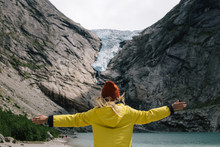Blonde Woman In Yellow Raincoat And Terracotta Hat Feels Freedom And Looks How Blue Ice Tongue Of Briksdal Glacier Slides From The Giant Rocky Mountain And Melts Into Cold Lake. Norway