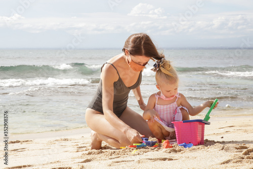 Fototapeta Summer vacation after Coronavirus pandemic crisis. Adorable toddler girl and her mum wearing protective mask while playing with beach toys on the sandy beach. obraz na płótnie