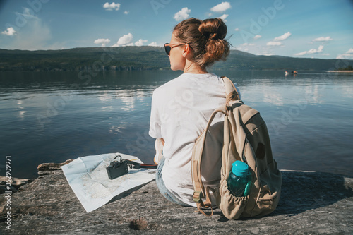 Fotografia Young woman traveler in a white T-shirt sits on the lake with a paper map and ca