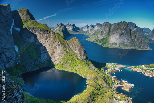 Obraz Reine, Lofoten, Norway. The village of Reine under a sunny, blue sky, with the typical rorbu houses. View from the top of Reinebringen mountain. - fototapety do salonu