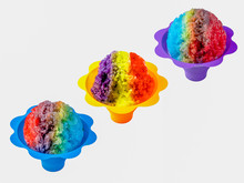 Three Rainbow Hawaiian Shave Ice, Shaved Ice Or Snow Cone Desserts In A Row Against A White Background.