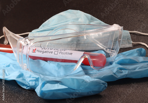 test tube with coronavirus, medical mask, thermometer and safety glasses #352916588