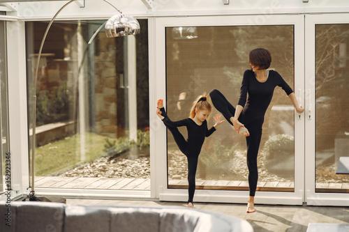 Obraz Girl is engaged in gymnastics. Family in a yoga studio. Kid in a black sportwear. - fototapety do salonu