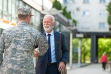 Senior Businessman Shaking Hands With Soilder Outdoor