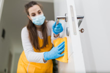 Close Up Of Woman With Protective Mask Cleaning Door. Coronavirus Prevention Concept.