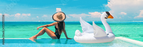 Obraz Luxury swimming pool vacation travel lady sun tanning relaxing on infinity ocean waterfront resort with floating white swan inflatable toy float banner panoramic summer background. - fototapety do salonu
