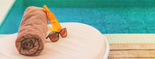 Suntan Summer Vacation Panoramic Of Swimming Pool Background. Luxury Banner Background Of Sunscreen, Sunglasses For Sun Protection On Towel And Lounger At Hotel For Sun Tan Relaxation.