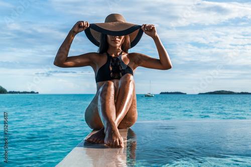 Fotografía Elegant black swimsuit swimwear model woman with contrast brim sun hat on infinity pool luxury resort vacation