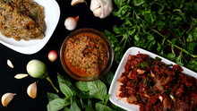 North-Eastern Food Of Thailand, Minced Catfish Spicy Salad With Herbs, Raw Beef In Spicy Condiment, Eggplant Soup Shoot Spicy Salad, With Vegetables And Herbs On A Dark Wooden Background Thaistreetfoo