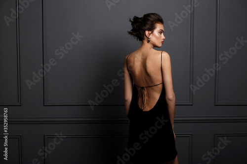 Cuadros en Lienzo Rear view of a sensual brunette young woman in sexy black dress with bare back and beautiful earrings nar grey dark neoclassical wall