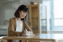 Senior Woman Writing Ending No...