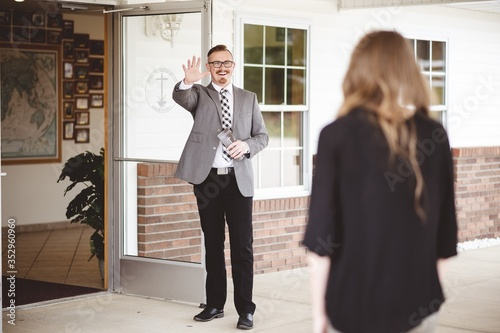 Fotografía Man in suit outside a church waving and welcoming a woman