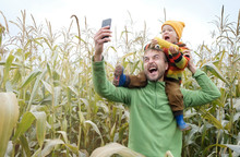 Father Carries Little Son In His Shoulders And Make Selfie While Walking Across Yellow Autumn Corn Field. Fall Season Concept.
