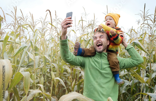Father carries little son in his shoulders and make selfie while walking across yellow autumn corn field Tapéta, Fotótapéta