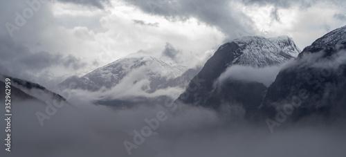 Wysokie szczyty górskie pokryte gęstą mgłą