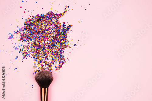 Closeup of professional cosmetic makeup brush with explosion of shiny colorful sparkles on bright pink background with copyspace for your text Canvas Print