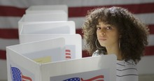 MS Young Hispanic Woman In Polling Station, Voting In A Booth With US Flag In Background. Serious Expression From High Viewpoint