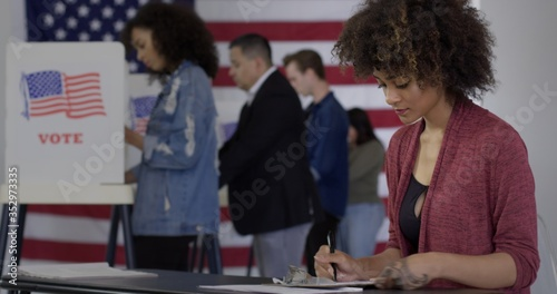 Fototapeta MS Young mixed-race woman staffing desk at polling station with various voters in background, US flag on wall behind them