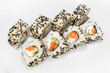 Japanese roll of rice, sesame seeds, cream cheese, cucumber, salmon on a white background