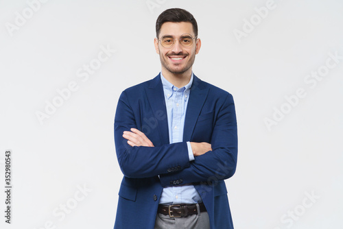 Fototapeta Portrait of young smiling businessman standing in front of the camera in blue blazer and casual shirt, holding arms crossed, isolated on gray background obraz