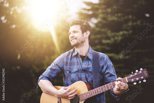 Cuadros en Lienzo Young male in a park holding a guitar and playing a song from the Christian hymn