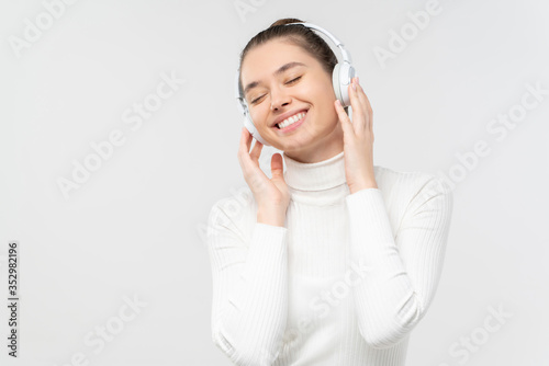 Photo Young female relaxing to sounds of music she is listening in wireless headphones