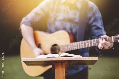 Fotomural Young male in a park holding a guitar and playing a song from the Christian hymn