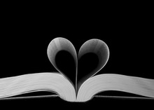 Closeup Shot Of Heart-shaped Book Pages On A Black Background