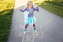Cute Adorable Little Young Child Girl Playing Hopscotch Outdoors. Funny Activity Game For Kids On Playground Outside. Summer Backyard Street Sport For Children. Happy Childhood Lifestyle.