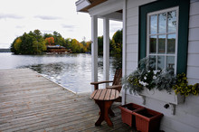 View Of The Lake From The Dock Of The Boathouse. Across The Water Is A Cottage Nestled Among Green Trees.