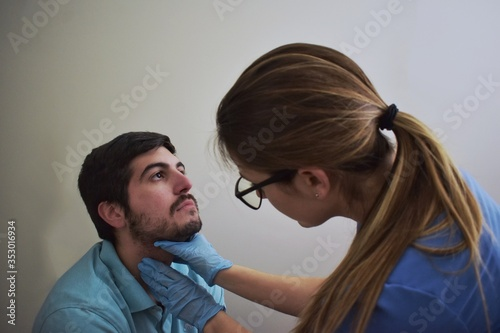 Clinician palpating patient's neck during a physical exam Canvas