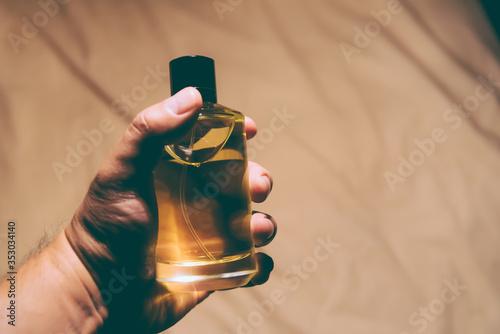 Obraz Man holding a bottle of perfume -  backlight - fototapety do salonu
