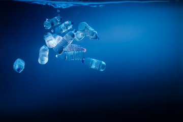 Plastic bottles sinking in to the ocean. Enviromental polution concept. World ocaens day